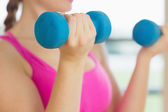 Mid section of a woman exercising with dumbbells in fitness stud — Stock Photo