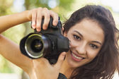 Gorgeous brunette woman holding her camera — Stock Photo
