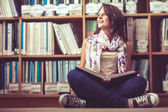 Thoughtful female student against bookshelf on the library floor — Stock Photo