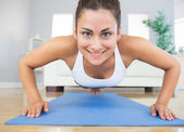 Fit young woman practicing press ups on a blue exercise mat — Stock Photo