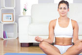 Calm young woman in sportswear sitting in lotus position on her — Stock Photo