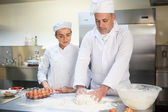 Head chef showing trainee how to prepare dough — Stock Photo