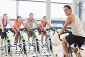 Man teaching spinning class to four people — Foto Stock