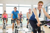 Happy woman teaches spinning class to four people — Stok fotoğraf
