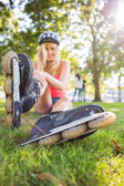 Casual pretty blonde wearing roller blades and helmet — Stock Photo