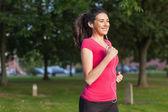 Motiverade sportiga kvinnan kör i en park — Stockfoto