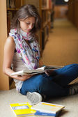 Female student reading a book in the library aisle — Stock Photo