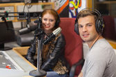 Attractive cheerful radio host interviewing a guest — Stock Photo