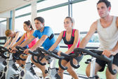 Determined people working out at spinning class — Stockfoto