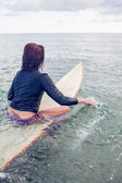 Rear view of a woman sitting on surfboard in water — Stock Photo