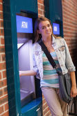 Pretty smiling student withdrawing cash smiling at camera — Stock Photo