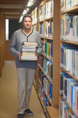 Attractive male librarian carrying a pile of books — Stock Photo