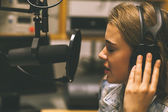 Focused pretty singer recording a song — Stockfoto