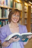 Cheerful mature female librarian posing holding an opened book — Photo