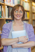 Зрелая женщина библиотекарь, позирует в библиотеке, держа планшет — Стоковое фото