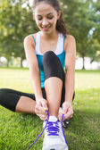 Active happy brunette tying her shoelaces — Stock Photo