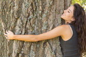 Casual content brunette embracing a tree with closed eyes — Stock Photo