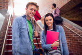 Couple with students behind on stairs in college — Stock Photo