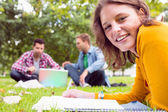 Female writing notes with students using laptop in park — Stock Photo