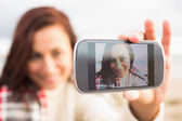 Woman self photographing with smartphone — Stock Photo
