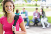 College girl smiling with blurred students in park — Stock Photo