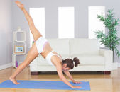 Sporty woman stretching her body with yoga pose on an exercise m — Stock Photo