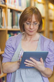 Female librarian using concentrated her tablet — Stock Photo