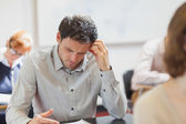 Concentrating handsome mature student sitting in classroom with — Stock Photo