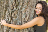 Casual gorgeous brunette embracing a tree with closed eyes — ストック写真