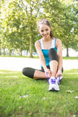 Smiling active brunette tying her shoelaces — Stock Photo