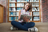 Happy student against bookshelf with tablet PC on the library fl — Stock Photo