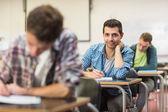 Mannelijke student met anderen schrijven nota's in de klas — Stockfoto