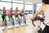 Man teaching spinning class to four people — Foto de Stock