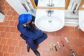 Plumber with cap repairing sink — Stock Photo