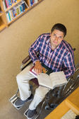 Portrait of a man in wheelchair reading a book in library — Stock Photo