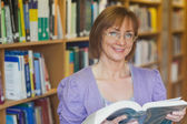 Calm female librarian posing holding an opened book — Photo