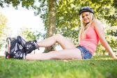 Casual smiling blonde wearing roller blades and helmet — Stock Photo
