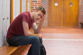 Frowning handsome student having a headache — Stock Photo