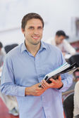 Cute male teacher holding some files while posing in his classro — Stock Photo