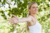 Young fit woman doing yoga in a park spreading her arms — Stock Photo