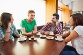 Four casual students having a cup of coffee chatting — Stock Photo
