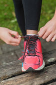 Close up of young woman tying her shoelaces — Stock Photo