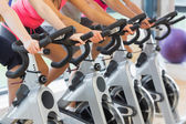 Mid section of people working out at spinning class — Stock Photo