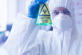 Scientist in protective suit with hazardous chemical in flask — Stock Photo