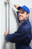 Smiling plumber repairing shower head — Stock Photo