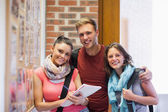 Three smiling students standing next to notice board — Stock Photo