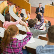 Students raising hands with a teacher in the lecture hall — Stock Photo #36182405