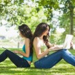 Two young brunette women sitting on a lawn — Stock Photo