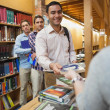 Attractive man handing a book to the female librarian — Stock Photo #36182829
