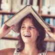 Cheerful student holding book over her head in library — Stock Photo #36183005